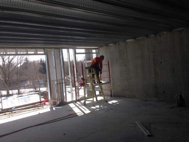 worker on a ladder near a balcony opening